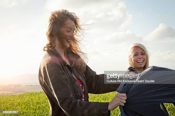 Two young women putting up tent in wind, Dorset, England