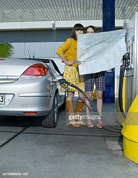Two young women reading map at petrol station