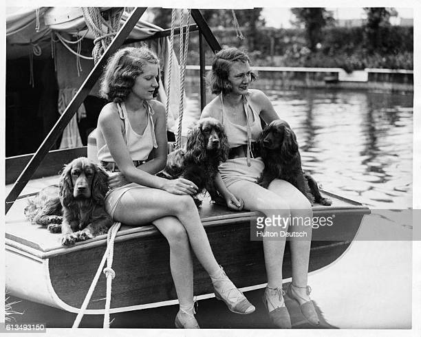 Two young women relax with their cocker spaniels during a holiday om the Norfolk Broads England 1935 | Location Norfolk Broads England UK