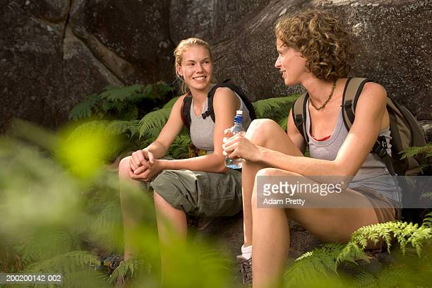 Two young women relaxing by rock face, sitting amongst ferns