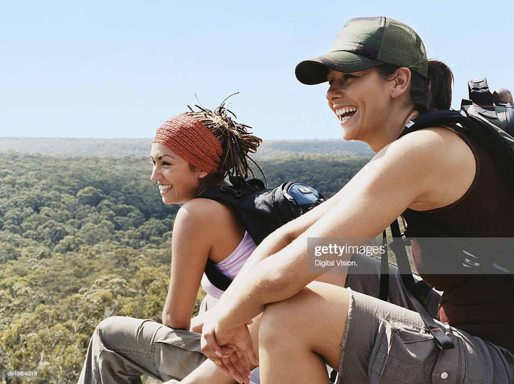 Two Young Women Relaxing From Hiking and Looking at the View Over Treetops : Stock Photo