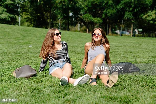 two young women relaxing in a park - women sunbathing stock photos and pictures