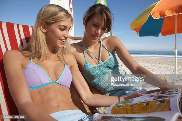 Two young women relaxing on beach, reading magazine