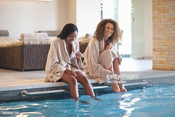 two young women relaxing on edge of spa swimming pool - bathrobe stock pictures, royalty-free photos & images
