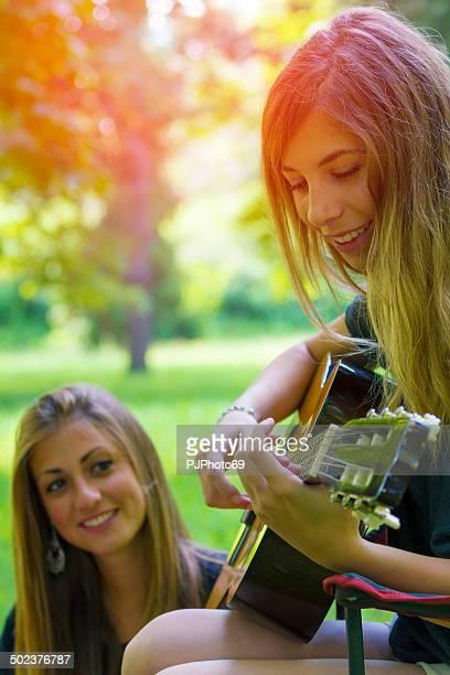 Zwei junge Frauen entspannenden spielt Gitarre