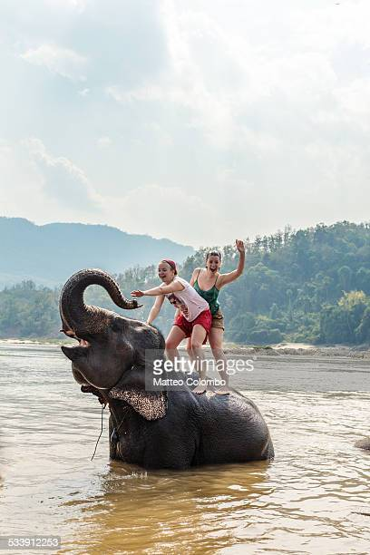 Two young women riding an elephant in the Mekong