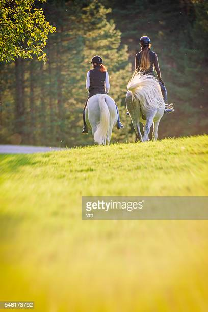 Two young women riding horses