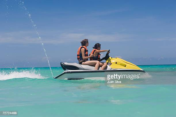 two young women riding jet boat, side view - jet ski stock pictures, royalty-free photos & images