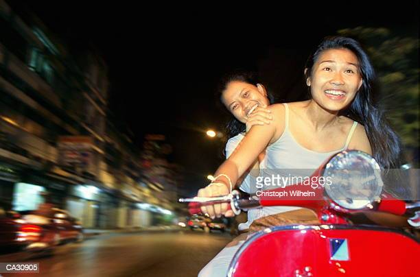 Two young women riding motor scooter, night (blurred motion)