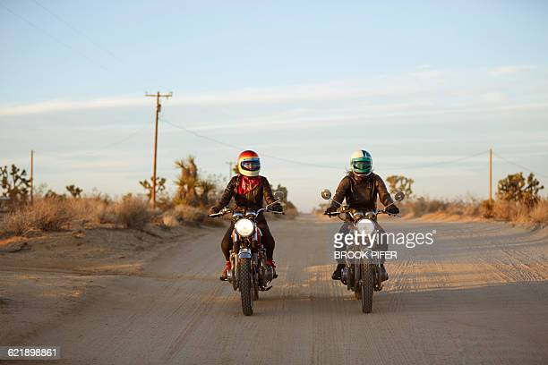 Two young women riding motorcycles on empty road