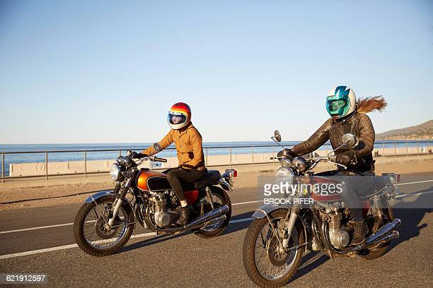 two young women riding motorcycles on empty road - crash helmet stock pictures, royalty-free photos & images