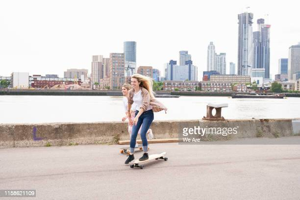 two young women riding skateboards - skating stock pictures, royalty-free photos & images
