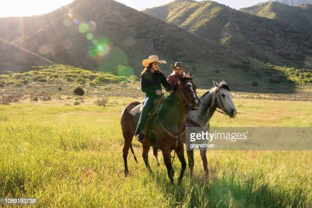 two young women riding their horses on the open range - andare a cavallo foto e immagini stock