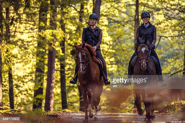 Two young women riding through forest