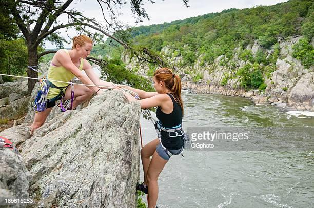 Two young women rock climbing
