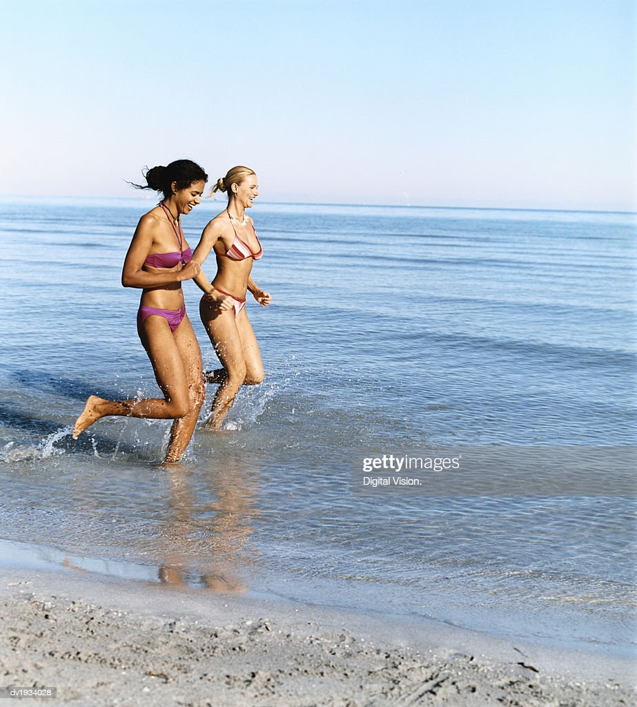 Two Young Women Running in the Sea : Stock Photo