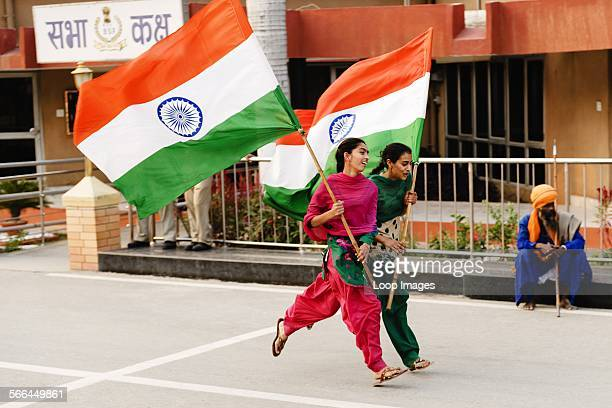 Two young women running waving the Indian Flag at the India and Pakistan border changing of the guards ceremony