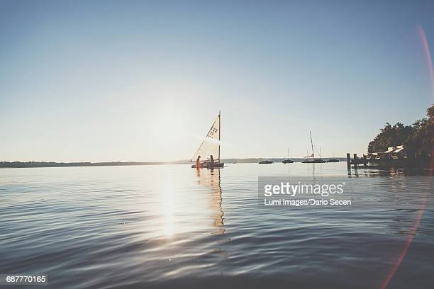 two young women sailing in dinghy at sunset - starnberg photos et images de collection