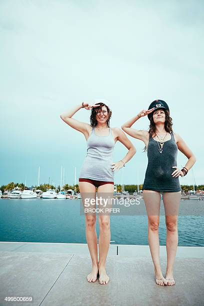 Two young women saluting on dock