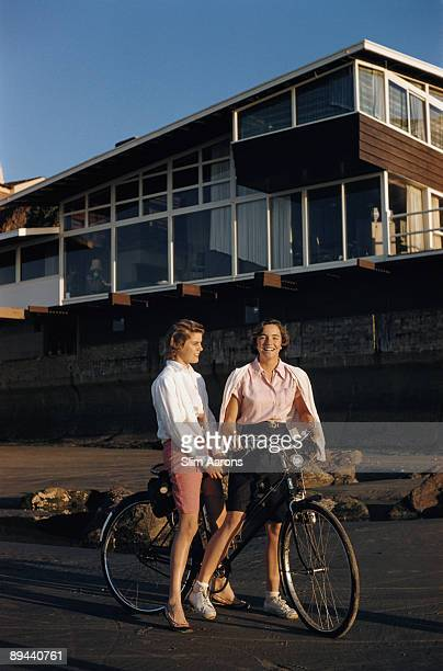 Two young women sharing a bicycle outside La Jolla Beach Tennis Club San Diego 1960