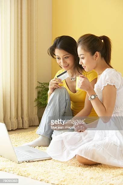Two young women shop together online.