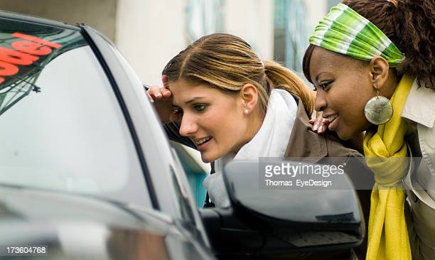two young women shopping for a new car, looking in window