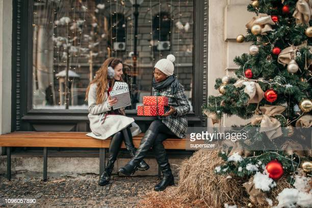 two young women shopping for christmas - exchanging stock pictures, royalty-free photos & images