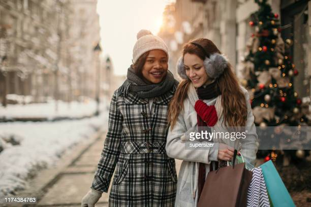 two young women shopping for christmas - white christmas stock photos and pictures
