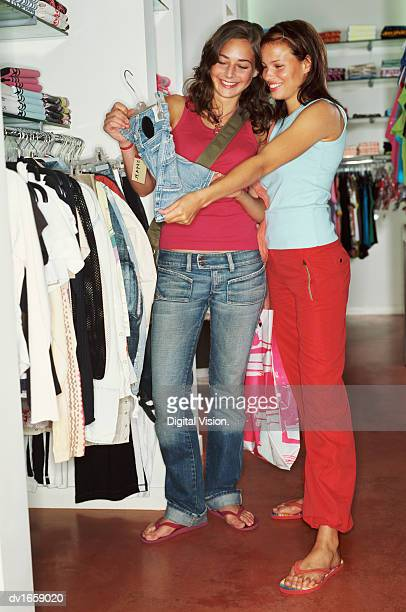 two young women shopping for clothes - girl wear jeans and flip flops stock photos and pictures