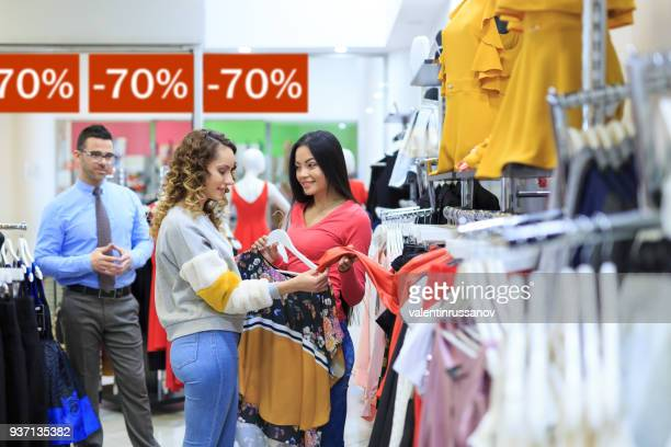 two young women shopping in store, looking for new clothes - percentage sign stock pictures, royalty-free photos & images