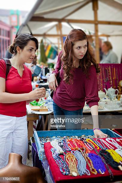 two young women shopping second hand at the flea market