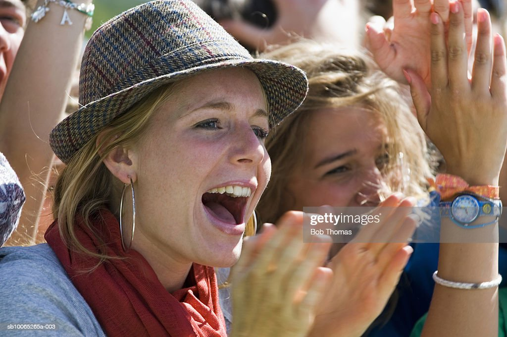 Two young women shouting and clapping hands, close-up (blurred motion) : Foto stock