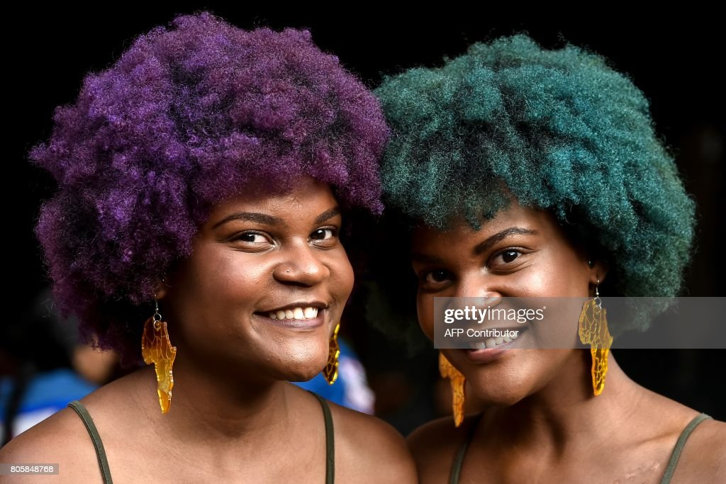 Two young women show Afro-Colombian hairstyles during the 13th contest of Afro hairdressers 'Tejiendo Esperanzas' (Weaving Hopes) in Cali, Valle del Cauca department, Colombia, on July 2, 2017. The contest seeks to revive African customs, identity and culture in Colombia. /