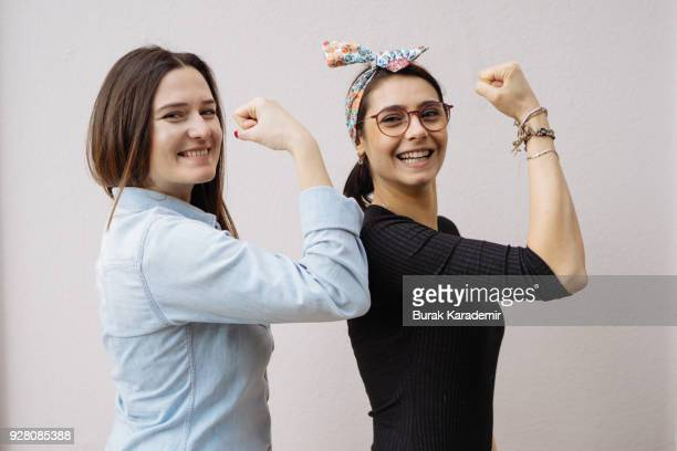 two young women show their strong arms - flexing muscles stock pictures, royalty-free photos & images