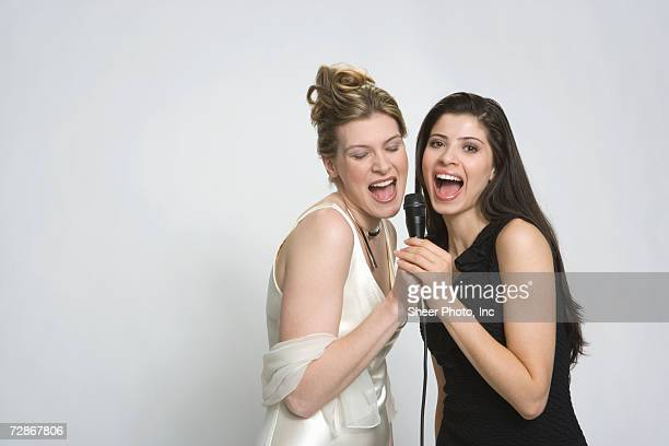 two young women singing into microphone, mouth open, close-up - inc mouth open photos et images de collection