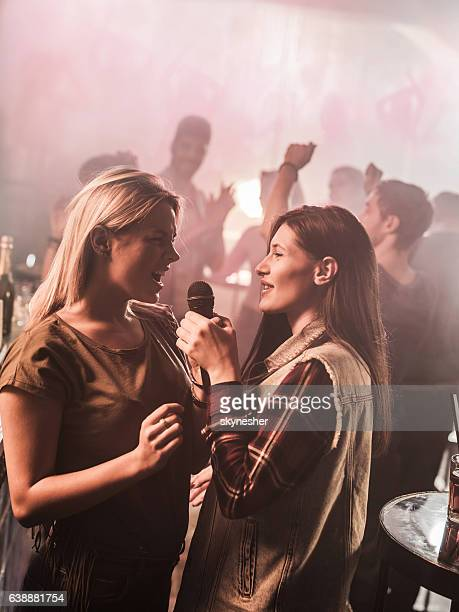 two young women singing karaoke at the disco. - incidental people stock pictures, royalty-free photos & images