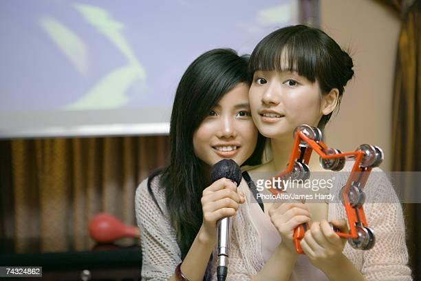 Two young women singing karaoke