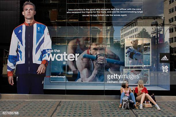 Two young women sit and rest from shopping beneath the inspiring image of Team GB gold medallist Ben Ainsley who adorns the exterior of the Adidas...