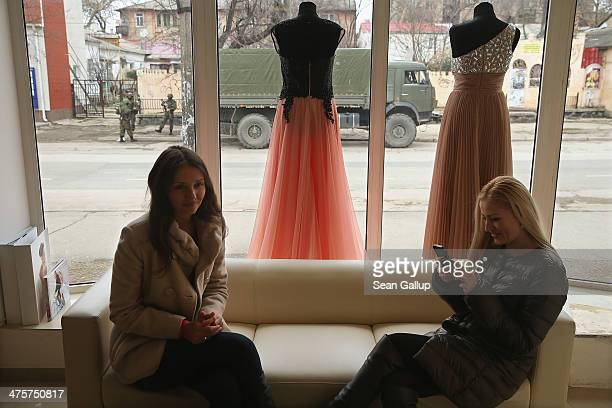 Two young women sit in a shop that sells evening gowns as heavily-armed soldiers displaying no identifying insignia stand outside in a street in the...