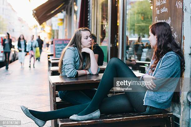 two young women sit in sidewalk cafe in berlin kreuzberg - kreuzberg stock photos and pictures