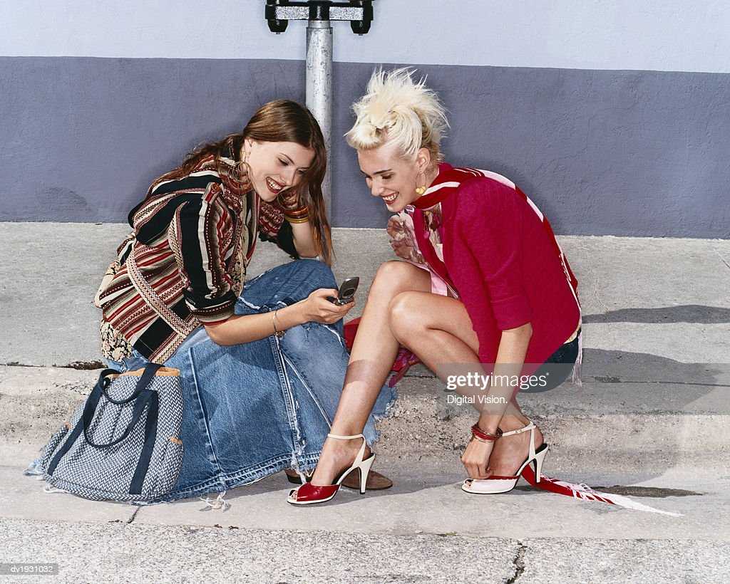 Two Young Women Sit on a Kerb, Texting on a Mobile Phone and Laughing : Stock Photo