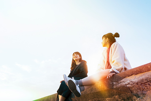 Two young women sitting and talking - gettyimageskorea