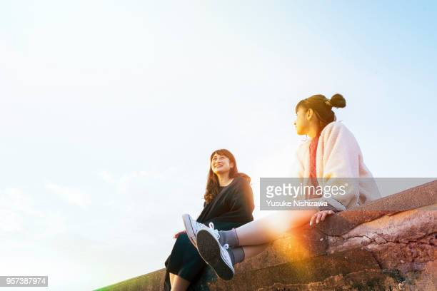 two young women sitting and talking - two people ストックフォトと画像