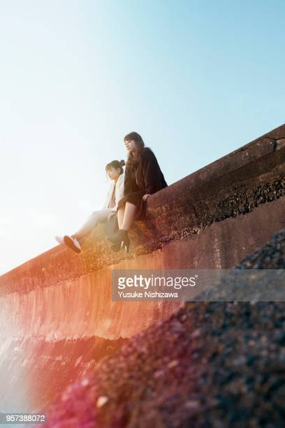 two young women sitting and talking - yusuke nishizawa stock pictures, royalty-free photos & images