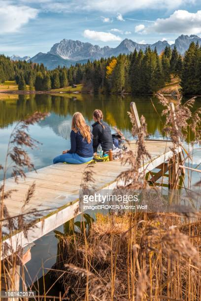 two young women sitting at a jetty having a snack, lake geroldsee, mittenwald, karwendel, bavaria, germany - karwendel mountains stock pictures, royalty-free photos & images