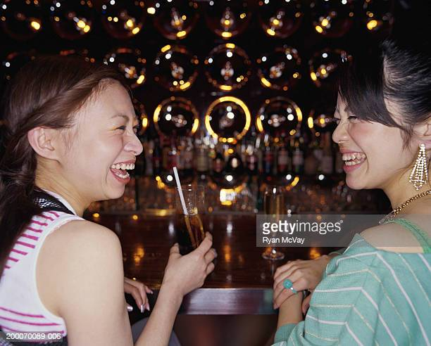 Two young women sitting at bar, drinking cocktails, side view