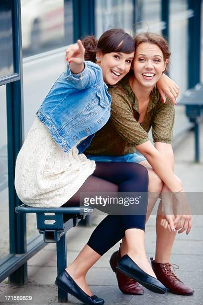 Zwei junge Frauen sitzen an der Bushaltestelle, Lachen, zeigt
