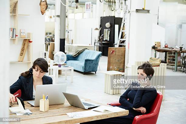 Two young women sitting at desk, using laptops
