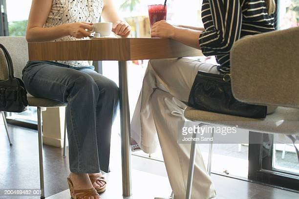 'Two young women sitting at table in bar, low section'