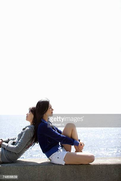 Two young women sitting back to back on breakwater by ocean, side view